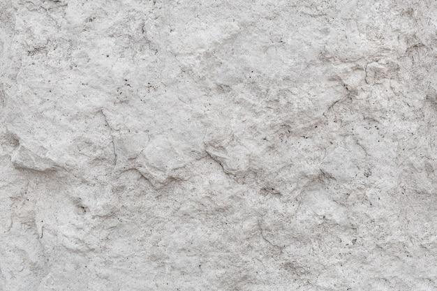 Szorstki nierówny kamień tekstura szarej betonowej ściany z bliska