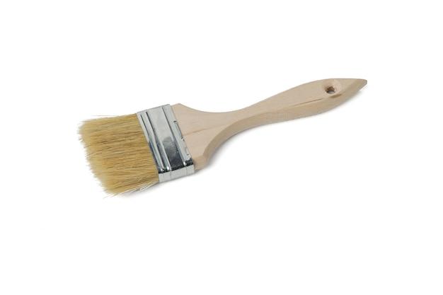 Szorstki pędzel z drewnianą rączką na białym tle na białej powierzchni