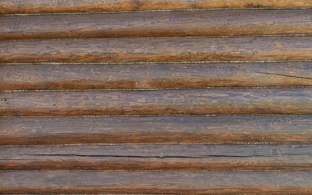Szorstki tło drewniane belki, brązowa ściana z bali tekstura.