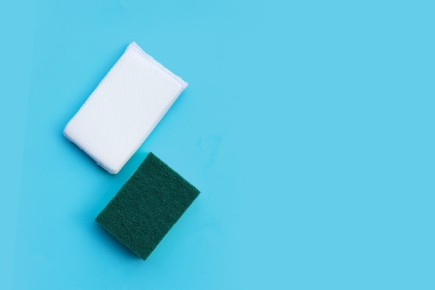Szoruj gąbki na niebieskim tle. kopiowanie miejsca, widok z góry