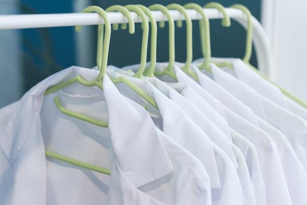 Szoruje na wieszakach. czyste białe fartuchy dla lekarzy. mundur medyczny