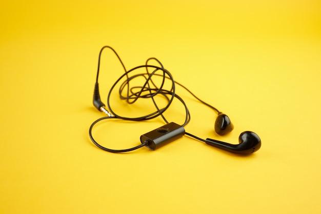 Szot słuchawek na jasnożółtym tle. ilustracja zamieszania. minimalna koncepcja