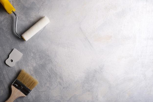 Szpachelki do nakładania szpachli oraz pędzle i wałki do malowania na szarym betonie