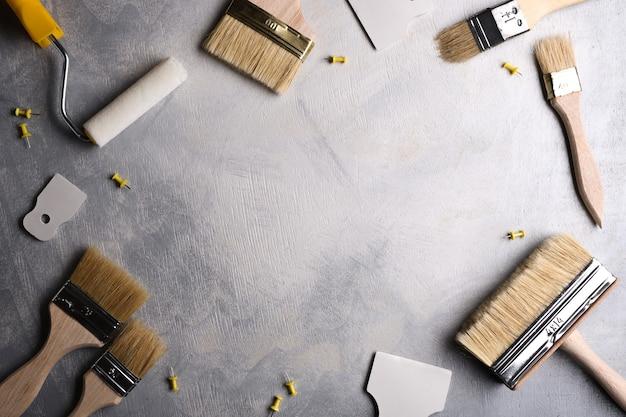 Szpachelki do nakładania szpachli oraz pędzle i wałki do malowania na szarym betonowym tle. widok z góry