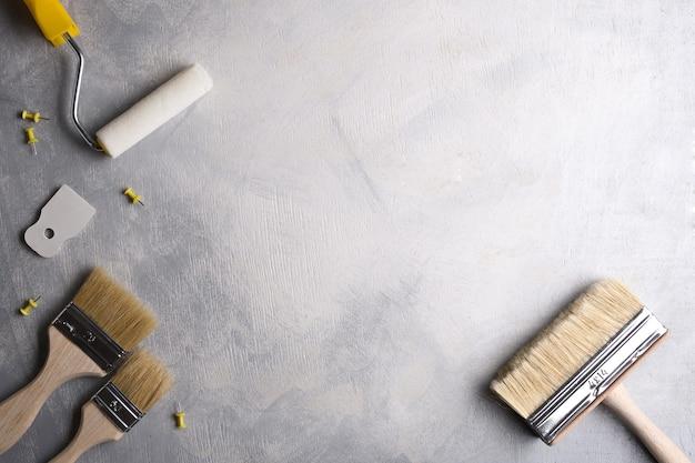 Szpachelki do nakładania szpachli oraz pędzle i wałki do malowania na szarym tle betonowym. widok z góry