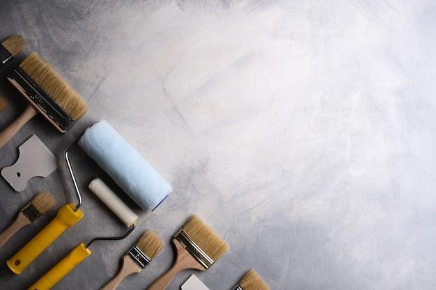 Szpachle do nakładania szpachli oraz pędzle i wałki do malowania na szarym betonie. widok z góry. leżał na płasko