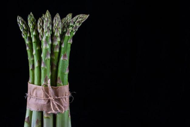 Szparag. bukiet świeżych zielonych szparagów wiązanej na czarnym tle.