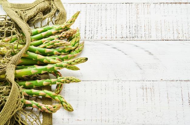 Szparag. świeże zielone szparagi kilka gotowych do gotowania na białym tle starych drewnianych. przestrzeń kopii widoku z góry.