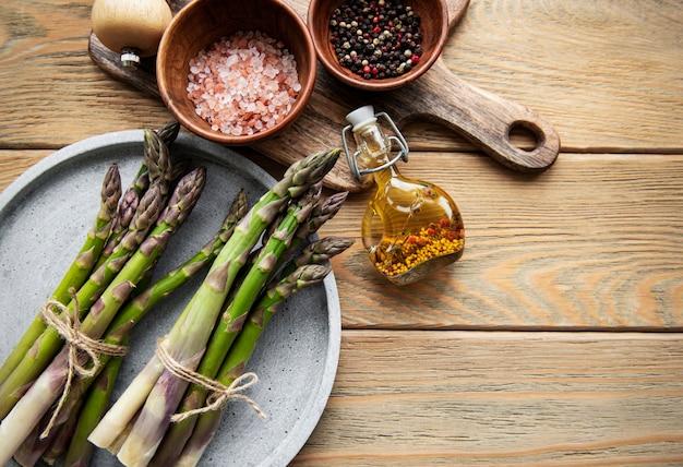 Szparagi i przyprawy na rustykalnym drewnianym stole