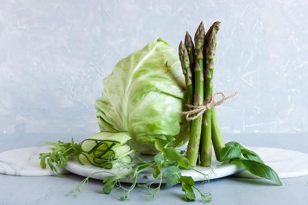 Szparagi, mikrogreeny, ogórek i kapusta to świeże zielone warzywa.