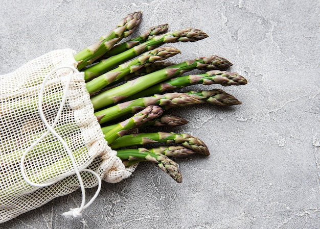 Szparagi wyrastają w ekologicznej siateczkowej torbie na betonowym stole