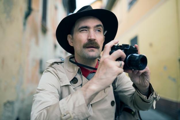Szpieg lub paparazzo fotograf, człowiek za pomocą aparatu na ulicy miasta