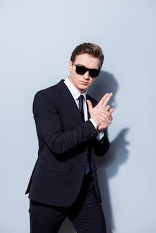 Szpieg policjant kryminalny detektyw z pistoletem ręcznym w eleganckim garniturze z krawatem i okularami przeciwsłonecznymi, stojący i pozujący odizolowany w czystej przestrzeni