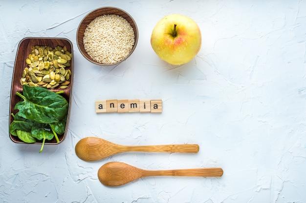 Szpinak, pestki dyni, sezam, jabłko i dwie drewniane łyżki na białym tle. koncepcja anemii. zbliżenie.