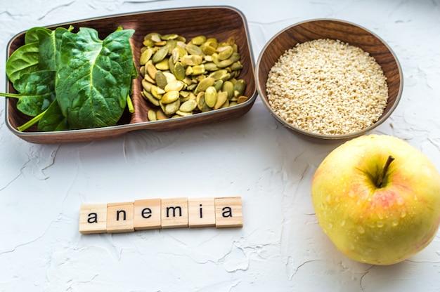 Szpinak, pestki dyni, sezam, jabłko na białym tle. koncepcja anemii. zbliżenie