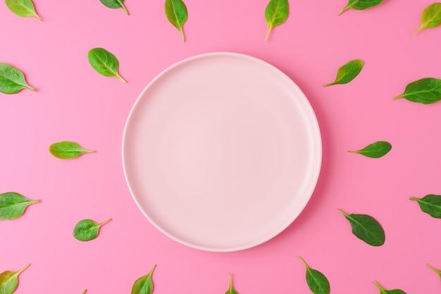 Szpinak pozostawia wokół pusty talerz na różowym tle