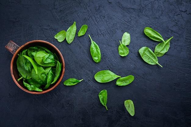 Szpinak w misce na ciemnym tle. umyty świeży mini szpinak, zielona trawa, sałatka z witaminami.