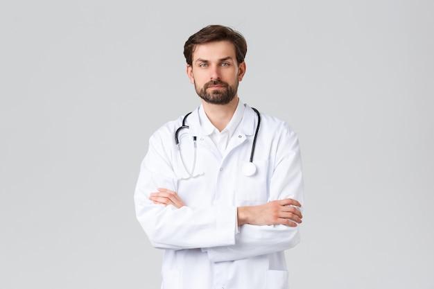 Szpital, pracownicy służby zdrowia, koncepcja leczenia covid-19. profesjonalny lekarz w białych zaroślach ze stetoskopem, krzyżowe ramiona w klatce piersiowej pewnie, patrząc na kamerę, leczące pacjentów, szare tło.