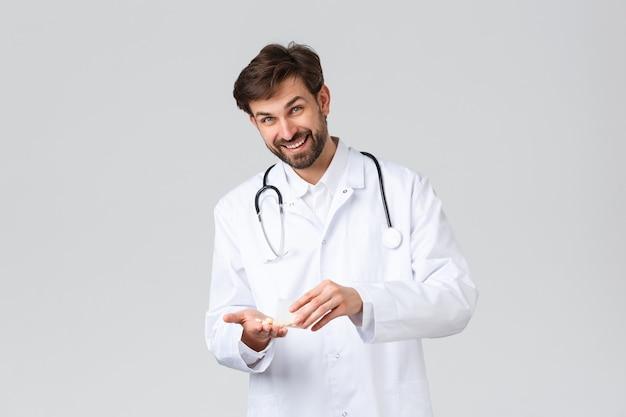 Szpital, pracownicy służby zdrowia, koncepcja leczenia covid-19. przystojny brodaty lekarz w białych zaroślach ze stetoskopem, pokazujący leki lub pigułki przepisane pacjentowi, aparat z uśmiechem, szare tło