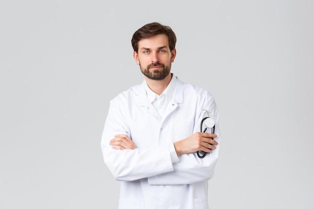 Szpital, pracownicy służby zdrowia, koncepcja leczenia covid-19. przystojny pewny siebie lekarz w białych zaroślach, stetoskop holdin, słuchanie pacjenta w gabinecie er lub lekarza, stojąc na szarym tle.