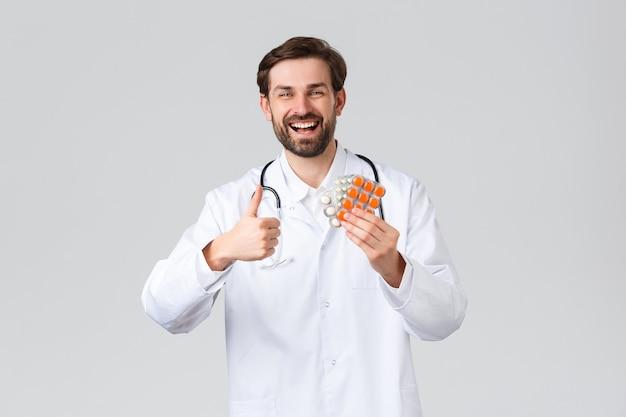 Szpital, pracownicy służby zdrowia, koncepcja leczenia covid-19. szczęśliwy wesoły kaukaski lekarz uśmiecha się, pokazuje kciuk w górę w aprobacie i doradza leki, witaminy lub tabletki, promuje służbę zdrowia