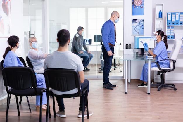 Szpitalna poczekalnia z pacjentami siedzącymi na krzesłach i pielęgniarką wyjaśniającą leczenie starszemu mężczyźnie noszącemu maskę przeciw covid-19