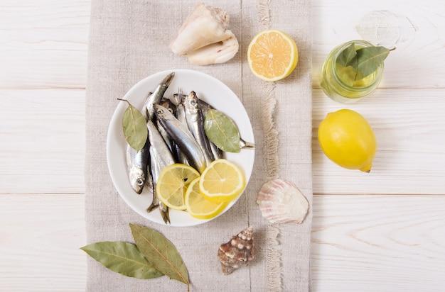 Szprot z przyprawami i cytryną, olej, muszla.
