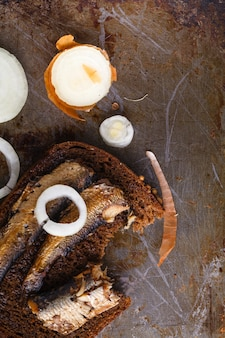 Szproty w puszce w puszce z chlebem żytnim. na rustykalnej powierzchni