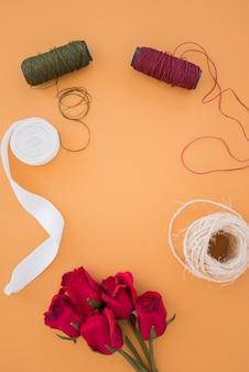 Szpule do przędzy; biała wstążka; szpula sznurkowa i czerwone róże na pomarańczowym tle