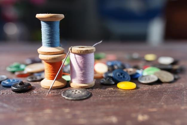 Szpule nici i guzików na starym drewnianym stole