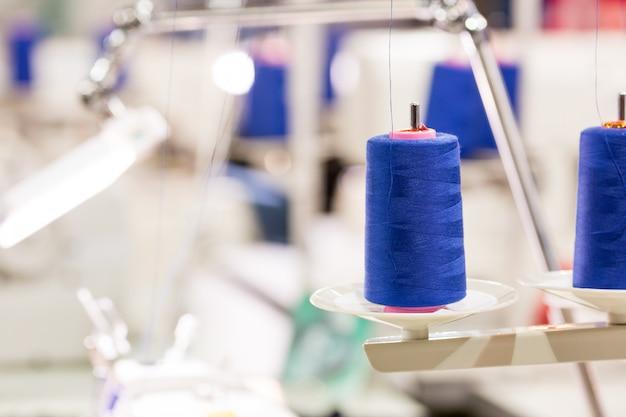Szpule niebieskiej nici na maszynie do szycia, fabryczne