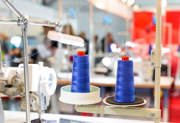 Szpule niebieskiej nici na maszynie do szycia. fabryka sukna, tkactwo, produkcja tekstyliów, przemysł odzieżowy