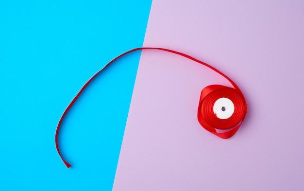 Szpule z czerwoną satynową wstążką w kolorze
