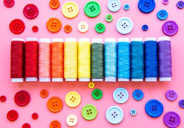 Szpule z nicią i guziki w kolorach tęczy