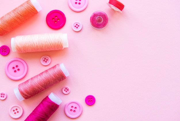 Szpule z nicią i guziki w różowych odcieniach na różowej powierzchni