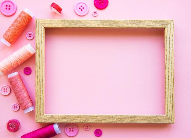 Szpule z nicią i guziki w różowych odcieniach na różowym, płaskim ułożeniu