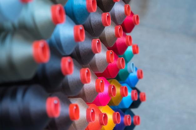 Szpulka z nicią hafciarską stosowana w przemyśle odzieżowym, rząd wielobarwnych rolek przędzy