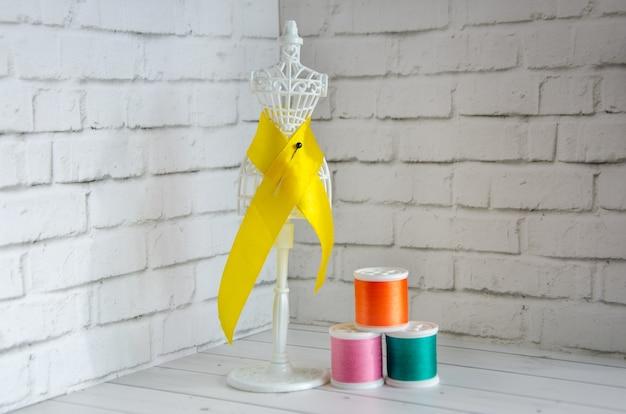 Szpulki kolorowej nici i miniaturowy manekin, wieszak do szycia ubrań. koncept: robótki ręczne, szycie, rękodzieło, rękodzieło. miejsce na tekst