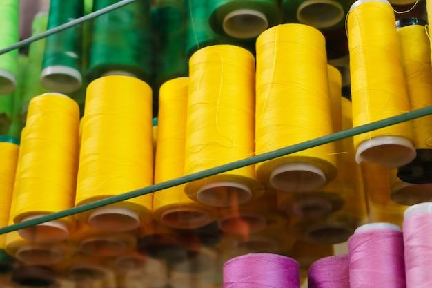 Szpulki przemysłowe z kolorowymi nićmi do szycia na szklanych półkach