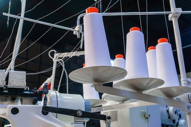 Szpulki z białymi nićmi zabezpieczone w przemysłowej maszynie do szycia w fabryce odzieży