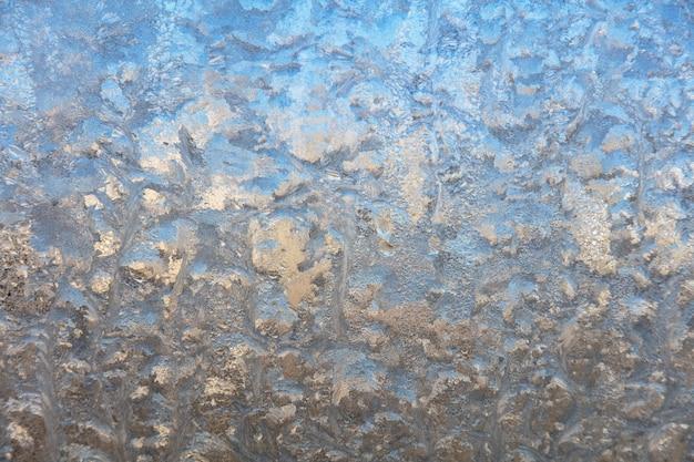 Szron rysujący się na szybie okna, ornament płatka śniegu po anomalii lodowatej.