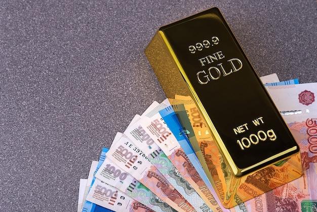 Sztabka złota i banknoty rubla rosyjskiego. banknoty są rozłożone w wachlarz i przypięte sztabką złota.