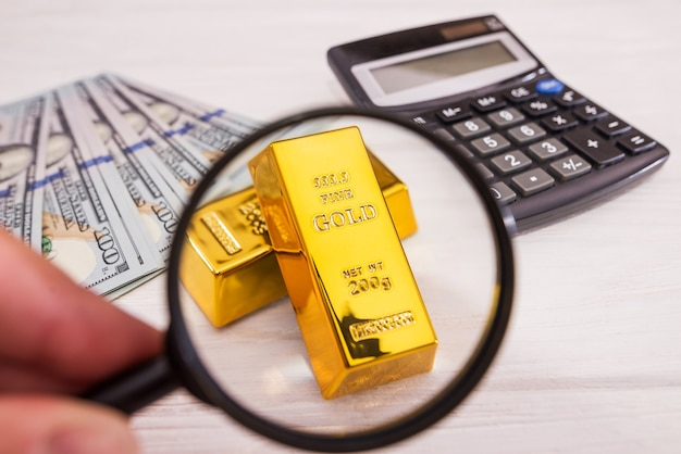 Sztabka złota na dolarach ze szkłem powiększającym