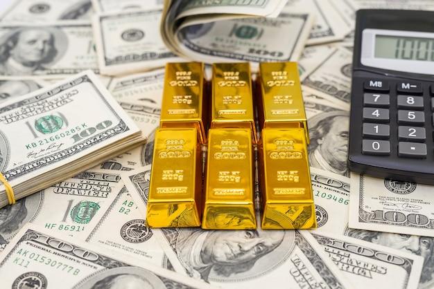Sztabki złota i kalkulator na 100 nowych banknotach dolarowych. koncepcja biznesu i finansów
