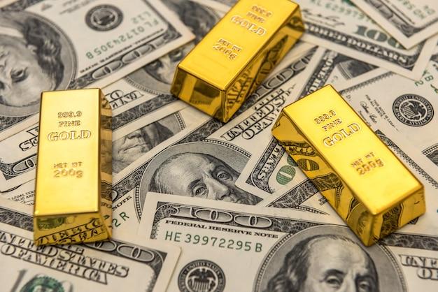 Sztabki złota leżącego na 100 dolarowych banknotach. bogactwo