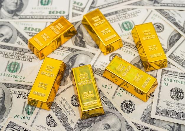 Sztabki złota na 100 nowych banknotach dolara amerykańskiego. koncepcja biznesu i finansów