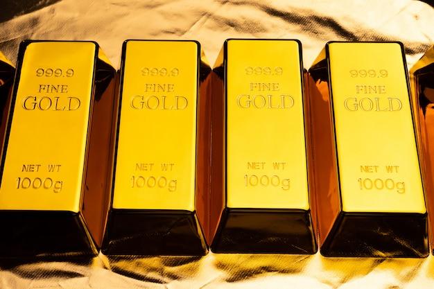 Sztabki złota na błyszczącym żółtym tle.