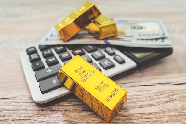 Sztabki złota z kalkulatorem i dolarami