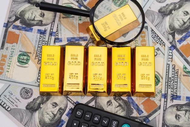 Sztabki złota z kalkulatorem i lupą na 100 nowych banknotach dolarowych. koncepcja biznesu i finansów