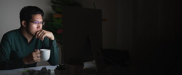 Sztandar atrakcyjny młody azjatykci mężczyzna pije kawowego obsiadanie